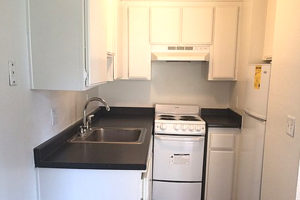 kitchen with white cabinets, black counters, sink, stove, and refrigerator