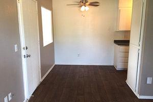 Dining area with dark hardwood floors, window, ceiling fan, adjacent to kitchen