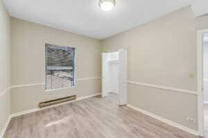 bright room with cream walls and wood floors facing window