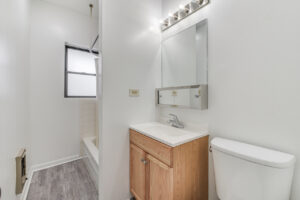 bright bathroom with tub, wood floors, brown cabinet on vanity