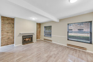bright room with wood floors, cream walls, facing windows and fireplace, small brick accent wall
