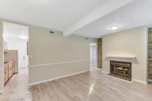 bright room with wood floors, cream walls, facing windows and fireplace