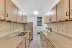 kitchen with brown cabinets lining both sides, facing window